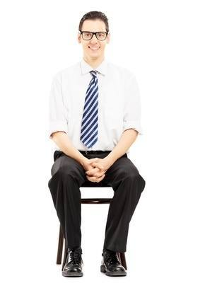 Young male with tie sitting on a wooden chair waiting for job in